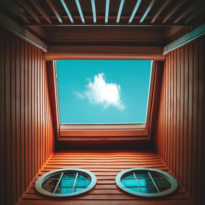 Breites Fenster mit zwei kleinen runden Fenstern mit einer Wolke