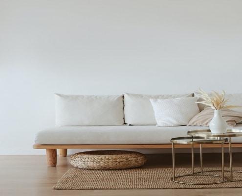 helles Zimmer mit Sofa und weißer Vase